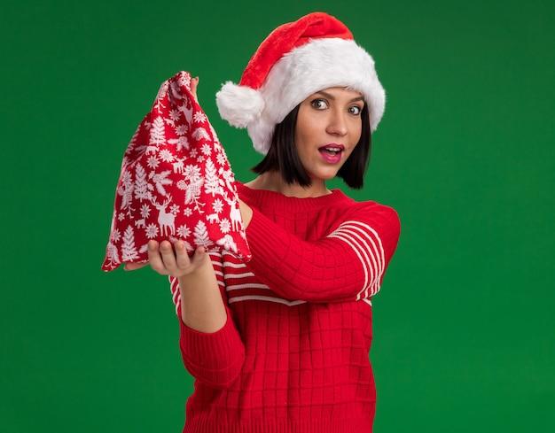 Pod wrażeniem młoda dziewczyna ubrana w santa hat wyciągając worek prezentów bożonarodzeniowych na białym tle na zielonej ścianie z miejsca na kopię