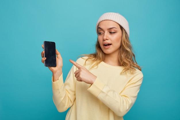 Pod wrażeniem młoda dziewczyna ubrana zimą kapelusz gospodarstwa patrząc i wskazując na telefon komórkowy