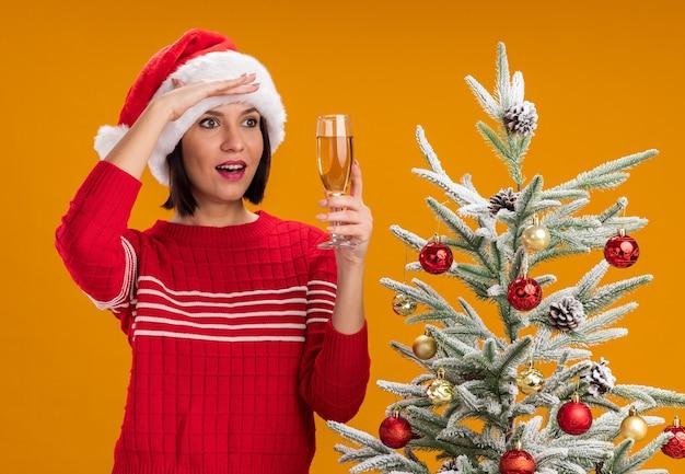 Pod wrażeniem młoda dziewczyna w czapce świętego mikołaja, stojąca w pobliżu udekorowanej choinki, trzymająca kieliszek szampana, trzymająca dłoń na czole, patrząc z boku na odległość, odizolowana na pomarańczowej ścianie