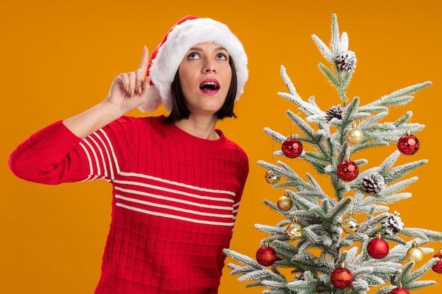 Pod wrażeniem młoda dziewczyna w kapeluszu świętego mikołaja stojąca w pobliżu ozdobionej choinki, patrząca i wskazująca w górę na białym tle na pomarańczowym tle