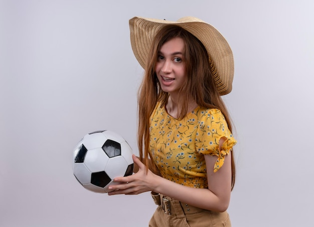 Pod wrażeniem młoda dziewczyna w kapeluszu trzyma piłkę nożną na odosobnionej białej przestrzeni
