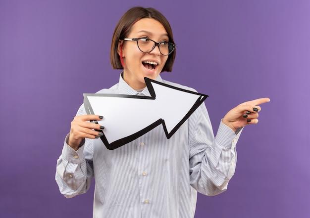 Pod wrażeniem młoda dziewczyna z call center w okularach, patrząc i wskazując na bok i trzymając znak strzałki, która wskazuje na bok na białym tle na fioletowo