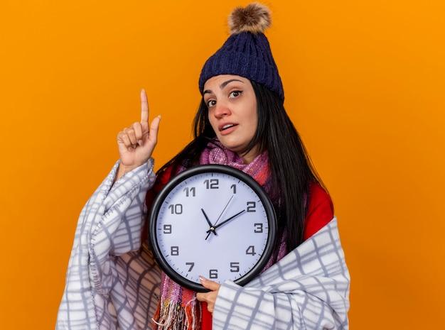 Pod wrażeniem młoda kaukaska chora dziewczyna w czapce zimowej i szaliku owinięta w kratę trzyma zegar patrząc na kamerę skierowaną w górę na białym tle na pomarańczowym tle z przestrzenią do kopiowania