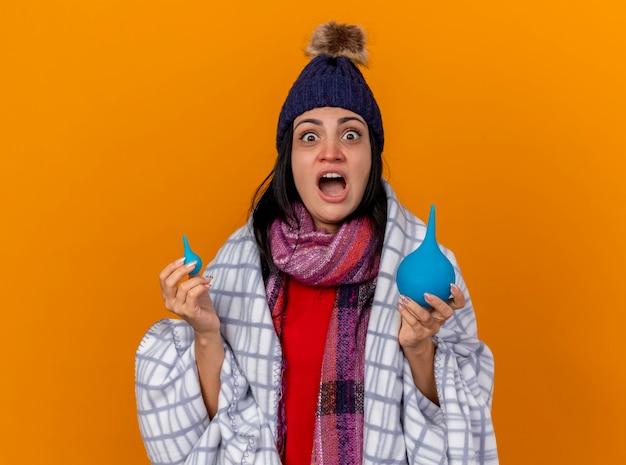 Pod wrażeniem młoda kaukaska chora dziewczyna w czapce zimowej i szaliku owinięta w kratę trzymając lewatywy patrząc na kamerę odizolowaną na pomarańczowym tle z przestrzenią do kopiowania