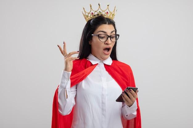 Pod wrażeniem młoda kaukaska dziewczyna superbohatera w okularach i koronie, trzymając i patrząc na telefon komórkowy, trzymając rękę w powietrzu na białym tle na białym tle z miejsca na kopię
