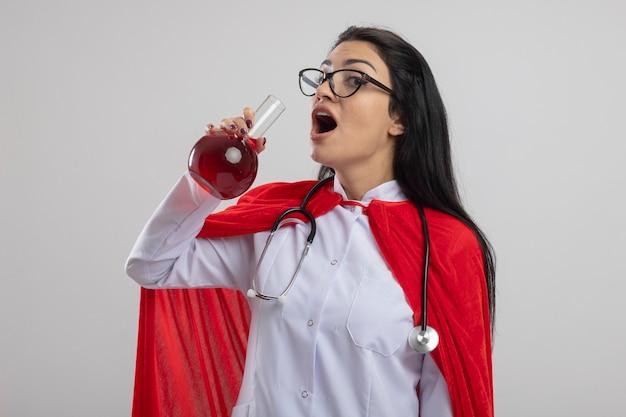 Pod wrażeniem młoda kaukaska dziewczyna superbohatera w okularach i stetoskopie trzymająca kolbę chemiczną z czerwonym płynem, próbująca go wypić, patrząc na kamerę na białym tle