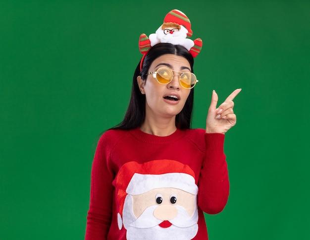Pod wrażeniem młoda kaukaska dziewczyna ubrana w opaskę świętego mikołaja i sweter w okularach patrząc i skierowaną w górę na białym tle na zielonym tle