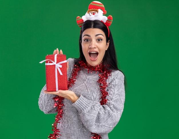 Pod wrażeniem młoda kaukaska dziewczyna ubrana w opaskę świętego mikołaja i świecącą girlandę na szyi trzymająca pakiet prezentów patrząc na kamerę odizolowaną na zielonym tle