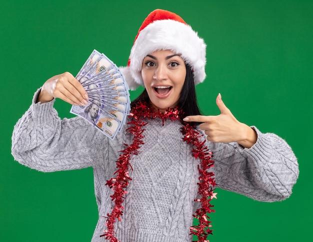 Pod wrażeniem młoda kaukaska dziewczyna ubrana w świąteczny kapelusz i świecącą girlandę wokół szyi, trzymając i wskazując na pieniądze, patrząc na kamerę odizolowaną na zielonym tle