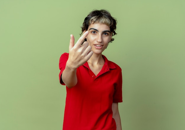 Pod wrażeniem młoda kaukaska dziewczyna z fryzurą pixie robi tu gest na aparat odizolowany na oliwkowym tle z miejsca na kopię