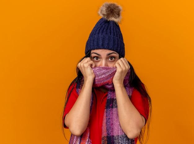 Pod wrażeniem młoda kaukaski chora dziewczyna ubrana w czapkę zimową i szalik zakrywający usta szalikiem na białym tle na pomarańczowej ścianie z miejsca na kopię