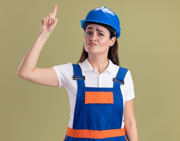 Pod wrażeniem młoda kobieta budowniczy w mundurach w górę odizolowane na oliwkowej ścianie