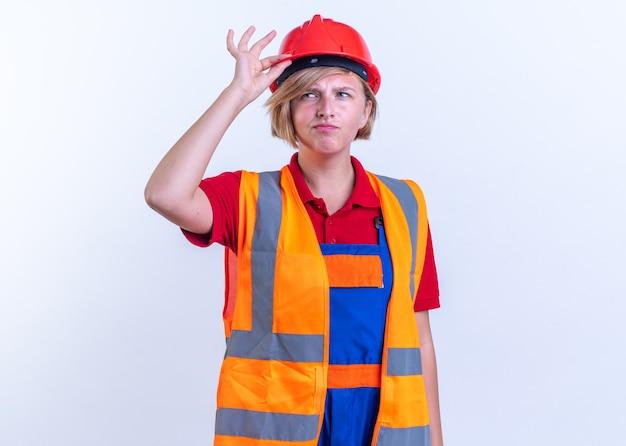 Pod wrażeniem młoda kobieta budowniczy w mundurze na białym tle