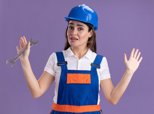 Pod wrażeniem młoda kobieta budowniczy w mundurze, trzymając klucz płaski, rozkładając ręce na białym tle na fioletowej ścianie