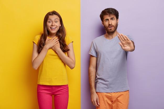 Pod wrażeniem młoda kobieta czuje się podekscytowana i szczęśliwa, trzyma ręce na piersi, poważny nieogolony mężczyzna wykonuje gest zatrzymania, stój blisko siebie