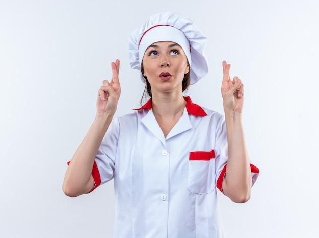 Pod wrażeniem młoda kobieta kucharz ubrana w mundur szefa kuchni skrzyżowanymi palcami na białej ścianie