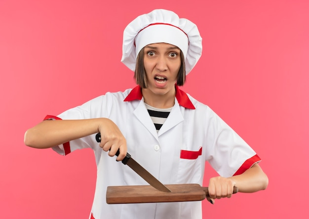 Pod Wrażeniem Młoda Kobieta Kucharz W Mundurze Szefa Kuchni Dotykając Deski Do Krojenia Nożem Na Różowym Tle Darmowe Zdjęcia