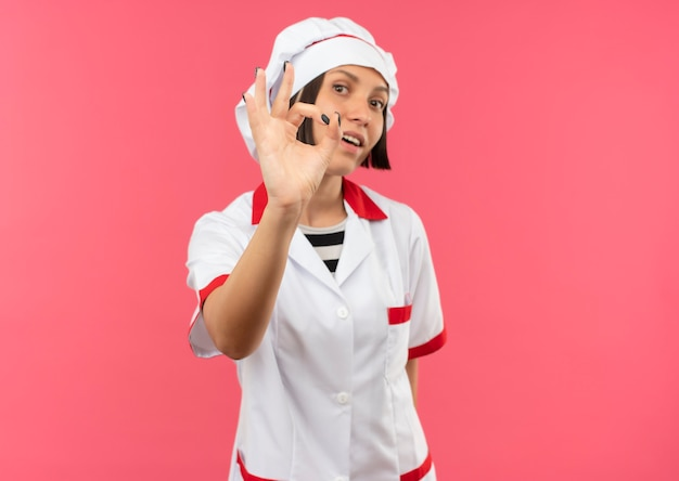 Pod wrażeniem młoda kobieta kucharz w mundurze szefa kuchni robi ok znak na różowym tle z miejsca na kopię