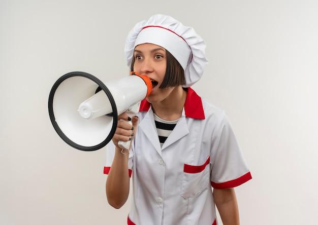 Pod wrażeniem młoda kobieta kucharz w mundurze szefa kuchni rozmawia przez głośnik patrząc na bok na białym tle na biały z miejsca na kopię