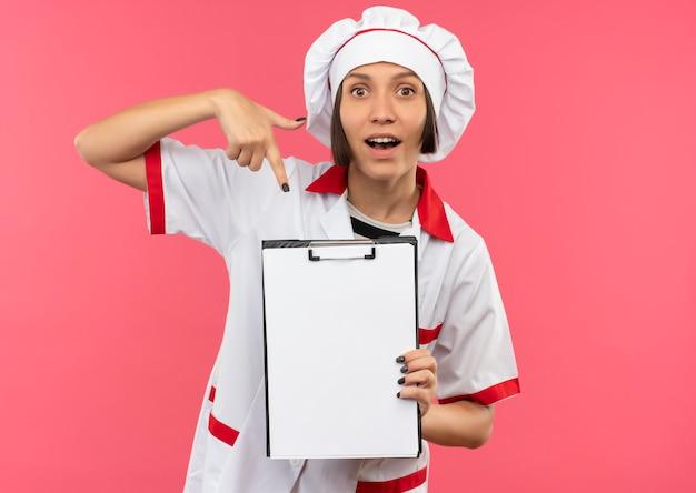 Pod wrażeniem młoda kobieta kucharz w mundurze szefa kuchni, trzymając i wskazując na schowek na różowym tle z miejsca na kopię