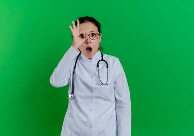 Pod wrażeniem młoda kobieta lekarz ubrana w szlafrok medyczny i stetoskop i okulary robi gest wygląd na białym tle na zielonej ścianie z miejsca na kopię