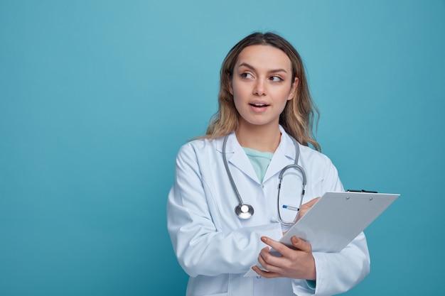 Pod wrażeniem młoda kobieta lekarz ubrana w szlafrok medyczny i stetoskop wokół szyi, trzymając schowka, wskazując piórem na nim patrząc na bok