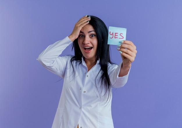 Pod wrażeniem młoda kobieta lekarz ubrana w szlafrok medyczny pokazujący tak notatkę, patrząc, trzymając rękę na głowie