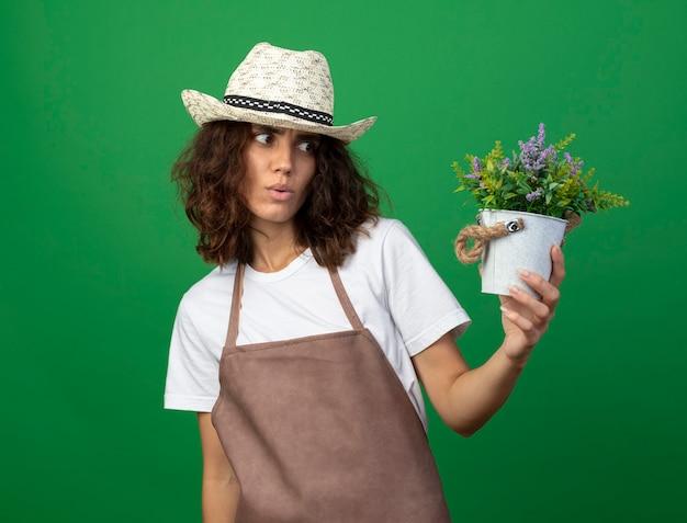 Pod wrażeniem młoda kobieta ogrodniczka w mundurze na sobie kapelusz ogrodniczy, trzymając i patrząc na kwiat w doniczce