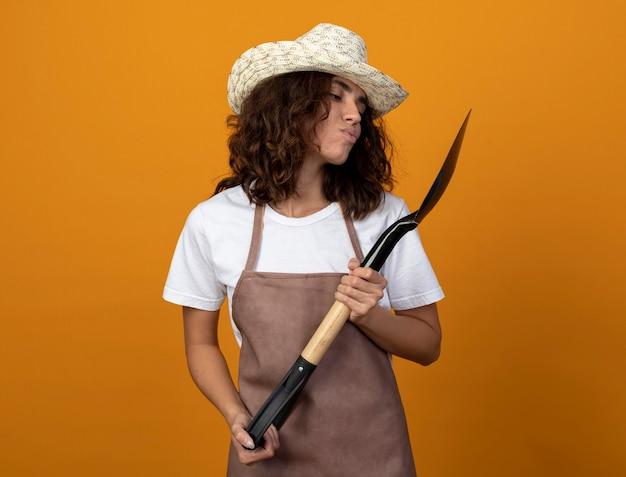 Pod wrażeniem młoda kobieta ogrodnik w mundurze na sobie kapelusz ogrodniczy, trzymając i patrząc na łopatę na białym tle na pomarańczowej ścianie