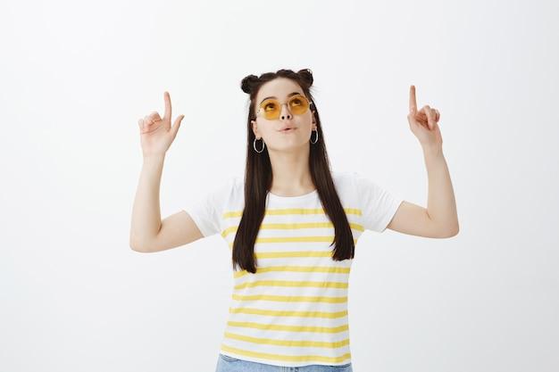 Pod wrażeniem młoda kobieta pozuje z okularami przeciwsłonecznymi na białej ścianie