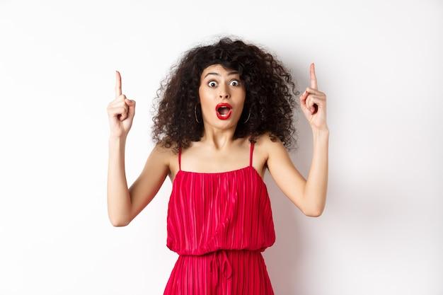 Pod wrażeniem młoda kobieta z kręconymi włosami, ubrana w czerwoną sukienkę, dysząca i mówiąca wow, wskazująca palcami w górę na logo, stojąca na białym tle.