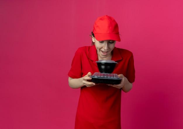 Pod wrażeniem młoda ładna dziewczyna dostawcza ubrana w czerwony mundur i czapkę, trzymająca i patrząca na pojemniki na żywność