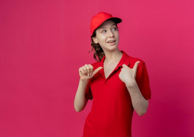 Pod wrażeniem młoda ładna dziewczyna dostawy ubrana w czerwony mundur i czapkę patrząc i wskazując na bok na białym tle na szkarłatnym tle z miejsca na kopię