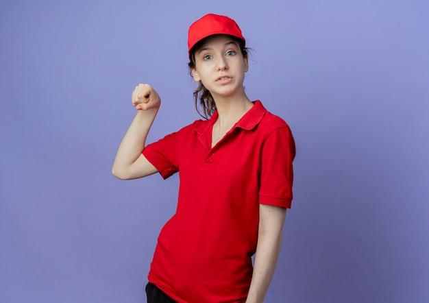Pod wrażeniem młoda ładna dziewczyna dostawy ubrana w czerwony mundur i czapkę udawać, że trzyma coś na białym tle na fioletowym tle z miejsca na kopię