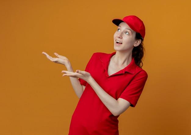 Pod wrażeniem młoda ładna dziewczyna dostawy w czerwonym mundurze i czapce patrząc i wskazując rękami na boku na białym tle na pomarańczowym tle z miejsca na kopię