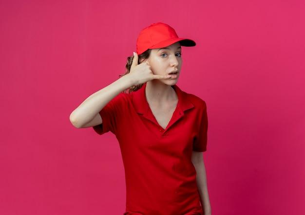 Pod wrażeniem młoda ładna dziewczyna dostawy w czerwonym mundurze i czapce robi gest połączenia