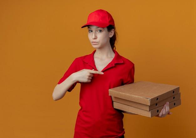 Pod wrażeniem młoda ładna dziewczyna dostawy w czerwonym mundurze i czapce, trzymając i wskazując na opakowania pizzy na białym tle na pomarańczowym tle z miejsca na kopię