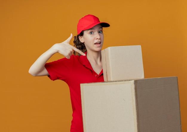 Pod wrażeniem młoda ładna dziewczyna dostawy w czerwonym mundurze i czapce, trzymając i wskazując na pudełka kartonowe na białym tle na pomarańczowym tle