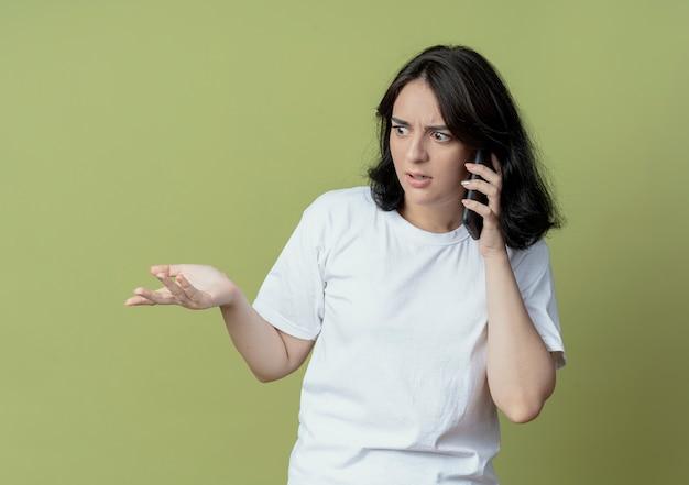 Pod wrażeniem młoda ładna dziewczyna kaukaski rozmawia przez telefon, patrząc z boku i pokazując pustą rękę na białym tle na oliwkowym tle