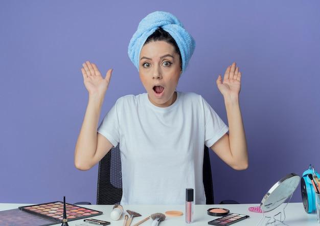 Pod wrażeniem młoda ładna dziewczyna siedzi przy stole do makijażu z narzędziami do makijażu i ręcznikiem kąpielowym na głowie pokazując puste ręce