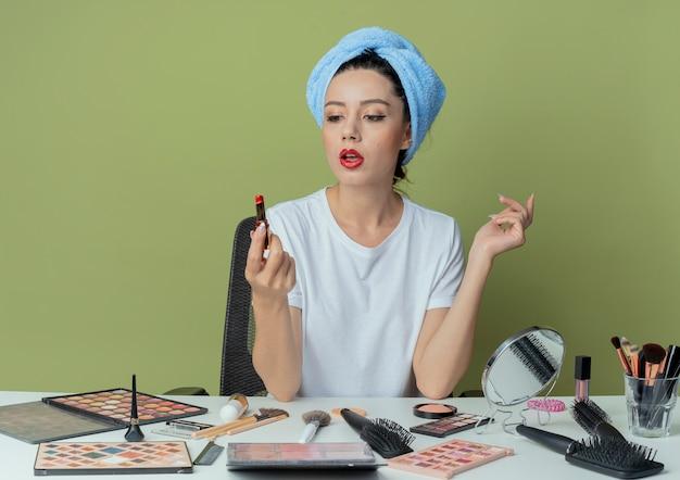 Pod wrażeniem młoda ładna dziewczyna siedzi przy stole do makijażu z narzędziami do makijażu i ręcznikiem na głowie, trzymając i patrząc na szminkę i trzymając rękę w powietrzu na oliwkowozielonej przestrzeni