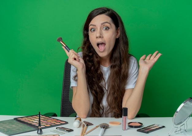 Pod wrażeniem młoda ładna dziewczyna siedzi przy stole do makijażu z narzędziami do makijażu, trzymając pędzel do różu i pokazując pustą dłoń na białym tle na zielonym tle