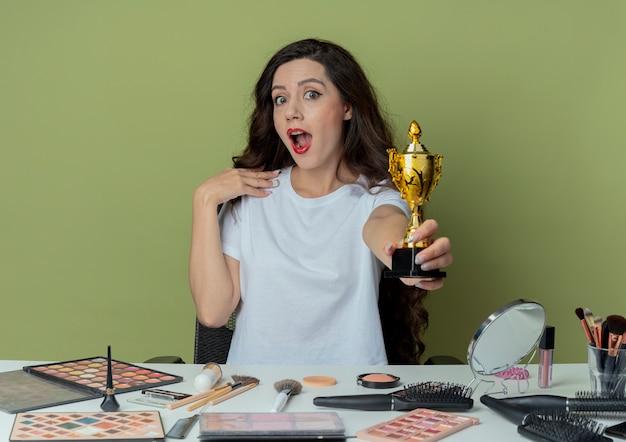 Pod wrażeniem młoda ładna dziewczyna siedzi przy stole do makijażu z narzędziami do makijażu, wyciągając puchar zwycięzcy w kierunku aparatu i dotykając brody odizolowanej na oliwkowym tle