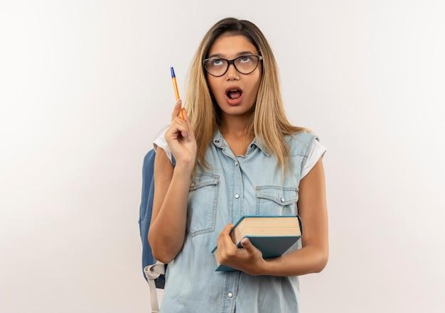 Pod wrażeniem młoda ładna dziewczyna student w okularach iz powrotem worek trzymając książkę i długopis patrząc w górę na białym tle