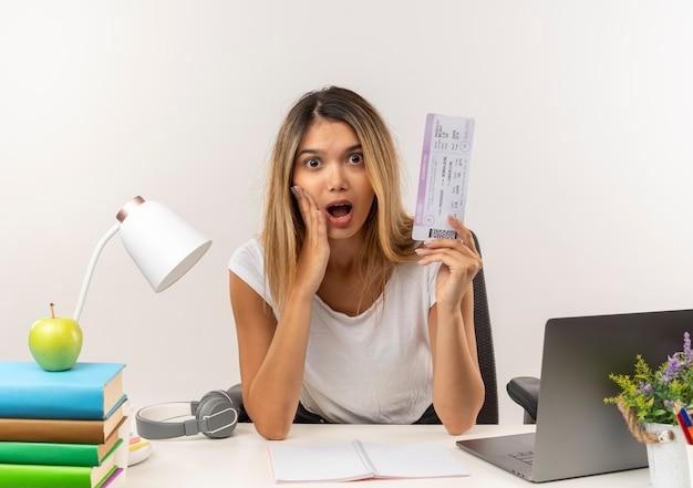 Pod wrażeniem młoda ładna dziewczyna studentka siedzi przy biurku z narzędziami szkolnymi, kładąc rękę na policzku i trzymając bilet lotniczy na białym tle