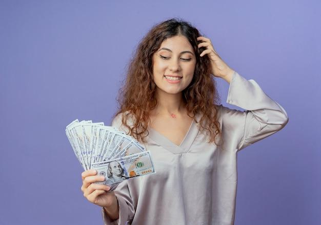 Pod wrażeniem młoda ładna dziewczyna trzyma i patrząc na gotówkę