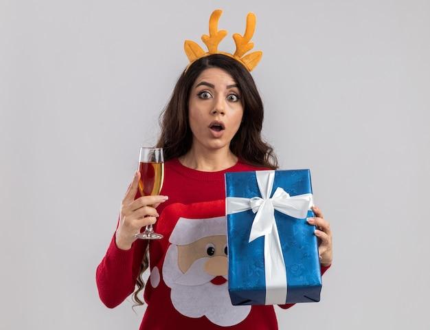 Pod wrażeniem młoda ładna dziewczyna ubrana w opaskę z poroża renifera i sweter świętego mikołaja trzymająca kieliszek szampana i wyglądający na prezent