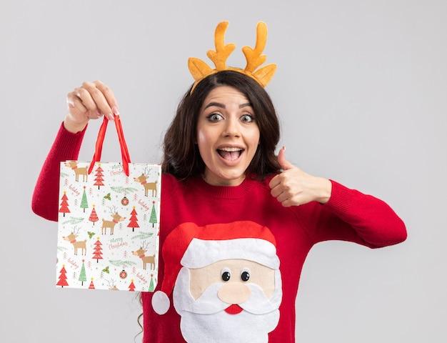 Pod wrażeniem młoda ładna dziewczyna ubrana w opaskę z poroża renifera i sweter świętego mikołaja trzymająca świąteczną torbę z prezentami, patrząc kciukiem w górę