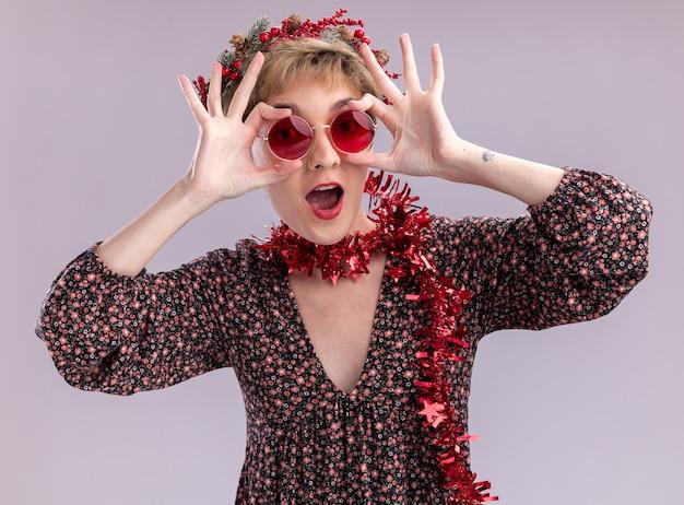 Pod wrażeniem młoda ładna dziewczyna ubrana w świąteczny wieniec na głowę i świecącą girlandę na szyi w okularach, patrząc na kamerę, chwytając okulary, wykonując gest spojrzenia na białym tle