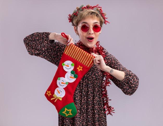 Pod wrażeniem młoda ładna dziewczyna ubrana w świąteczny wieniec na głowę i świecącą girlandę na szyi w okularach trzymająca skarpetę świąteczną, patrząc na kamery na białym tle